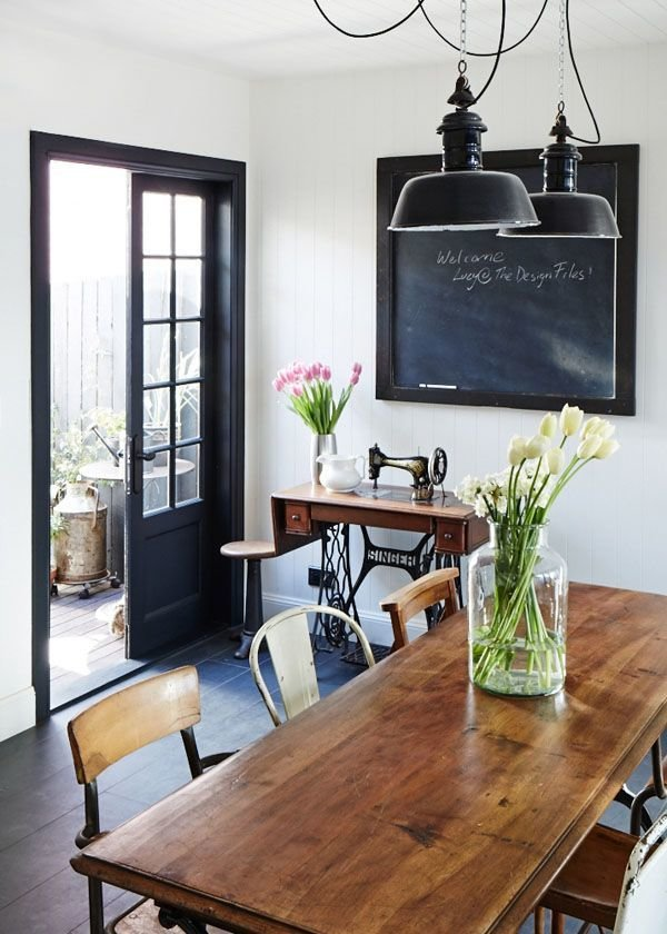 Black sash sliding doors into dining room with large wooden lacquered table and plants as decoration