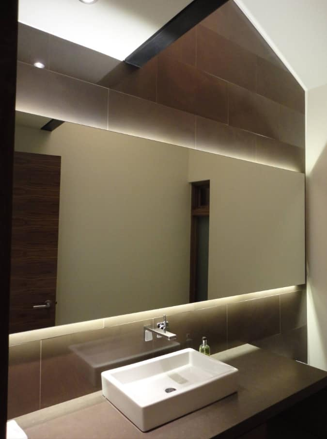 5 Enlightening Benefits of Hanging Lighted Mirrors on your Walls. Gorgeous large mirror at the brown tiled wall of the bathroom