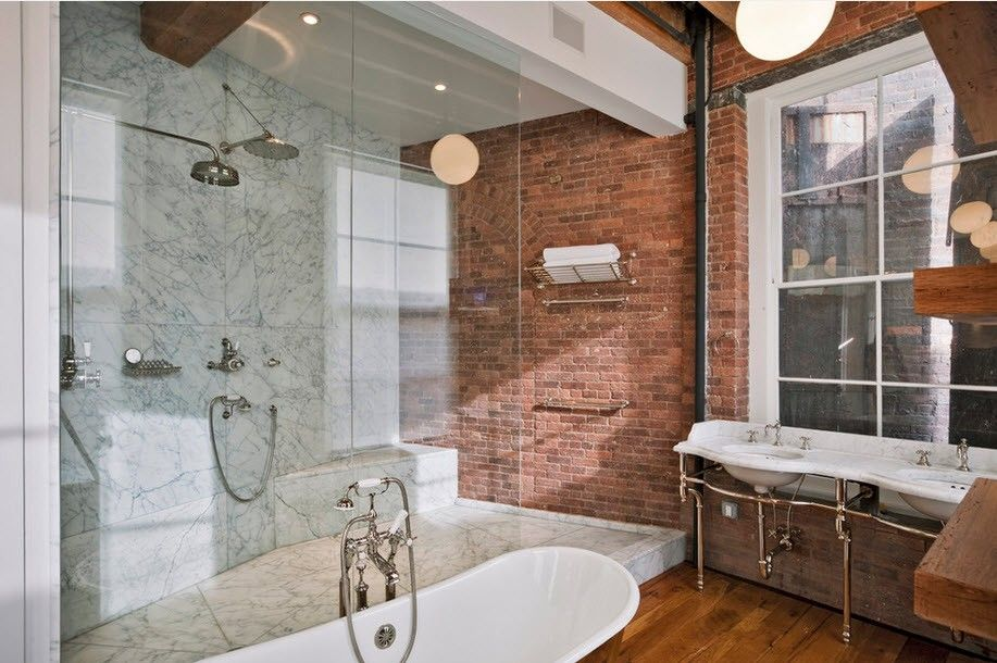 Glass delimited shower zone and open brickwork wall for industrial bathroom