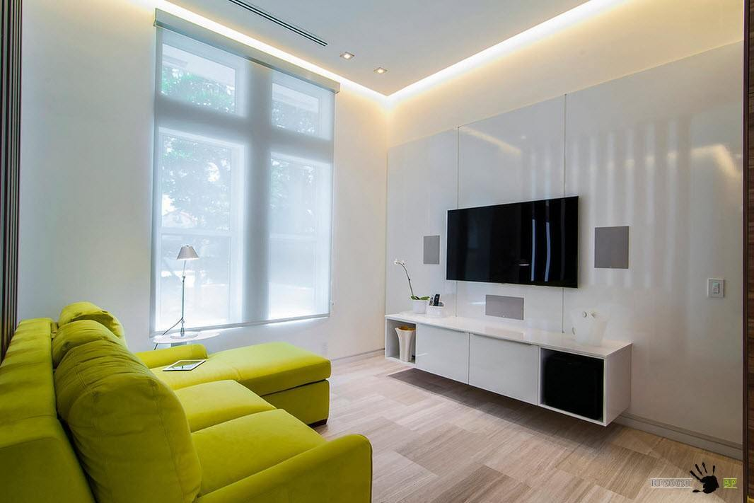 White glossy textured accent wall with black panel of TV in the modern tiny living with lime couch