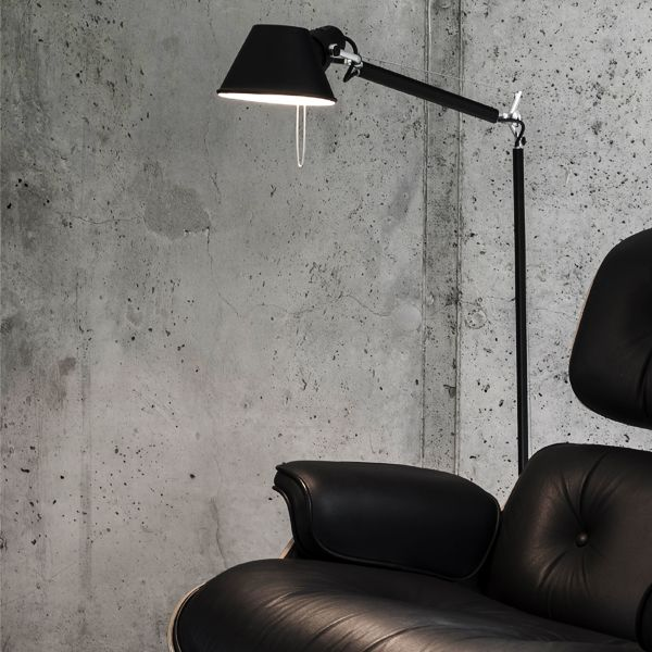 Great industrial design of the room with black sofa and floor lamp