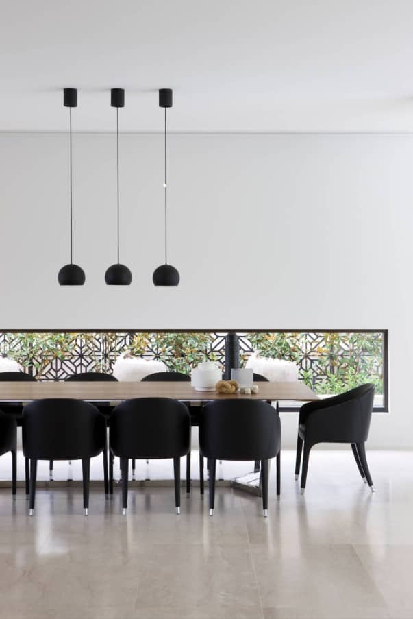All the contrast in the dining room with black lamps and chairs and grey walls