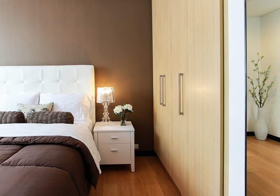 Tips To Get Your Guest Room Ready. Neat coffee with milk colored cebinet and brown accent wall for contemporary minimalistic bedroom with white furniture