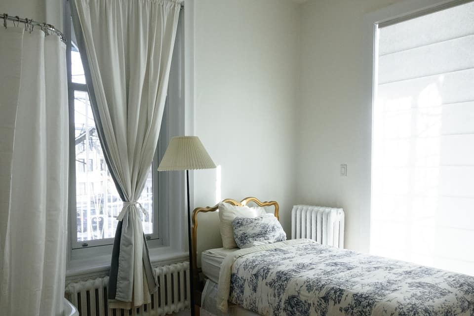 Tips To Get Your Guest Room Ready. Classic atmosphere in simple styled bedroom with floor lamp