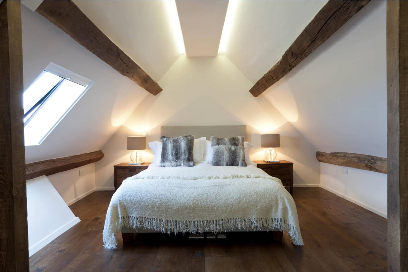 Tips To Get Your Guest Room Ready. Barn country style in the loft located white bedroom with wooden floor and laquered ceiling beams