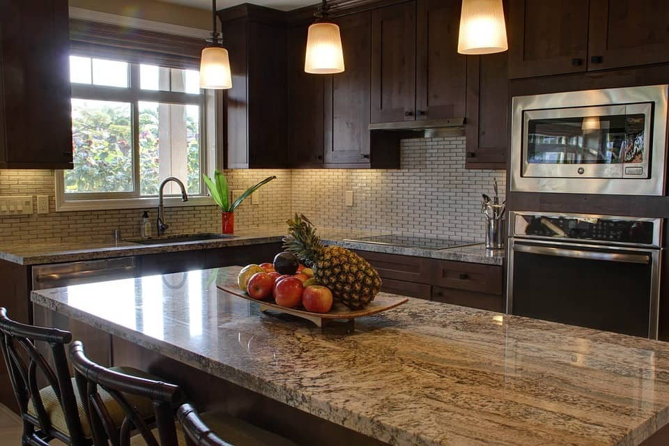 The Relevance and Advantages of Kitchen Renovation. Fruits on the marble countertop of dark wooden decorated kitchen