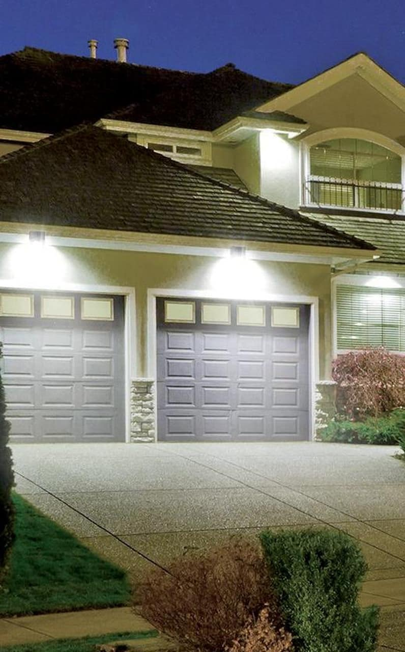 LED Wall Pack for your Home: Increase Ourdoor Lighting and Safety. Classic American styled house with double-door garage enlighted
