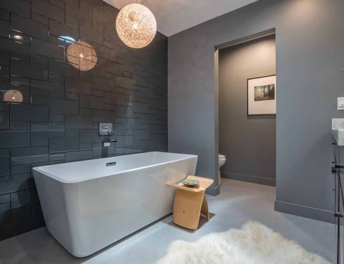 Exquisitely designed vanity stool near the white artificial stone bathtub in ultramodern bathroom