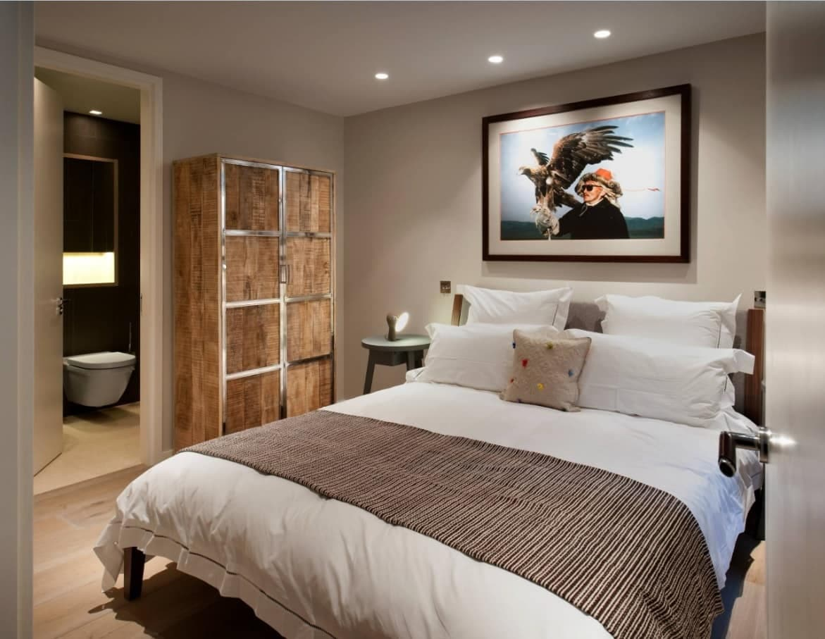 How to Create the Perfect Guest Bedroom. Brown and gray successful combination in the room with wooden cabinet and large bed