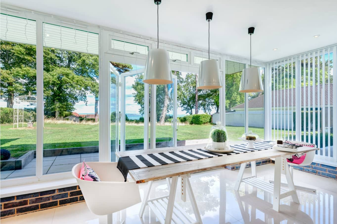 Saving Up with Window Blinds. Spacious modern style dining room with panoramic windows and glass door in white