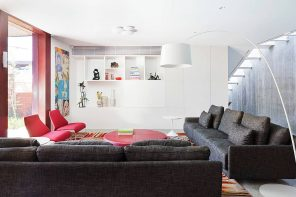 Your Dream Home: How Too Many Customizations Can Make It Hard to Sell. Stunning modern interior in white with a lot of storage spaces and dark sofa in living zone