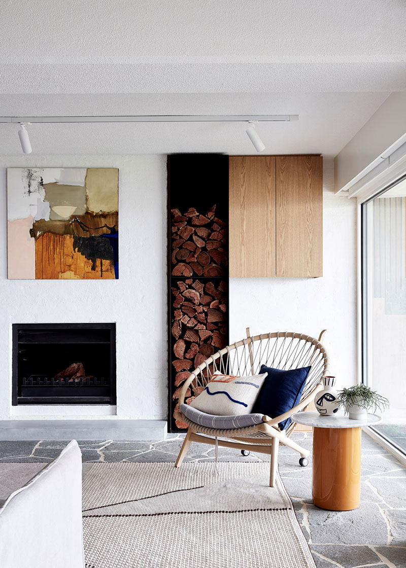 White painted walls for Scandi styled living room with firewood storage rack built right into the wall