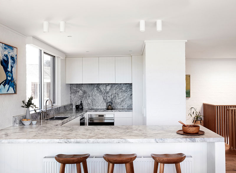 Large kitchen in minimalistic Scandinavian style with the dining zone at the marble topped island with wooden stools