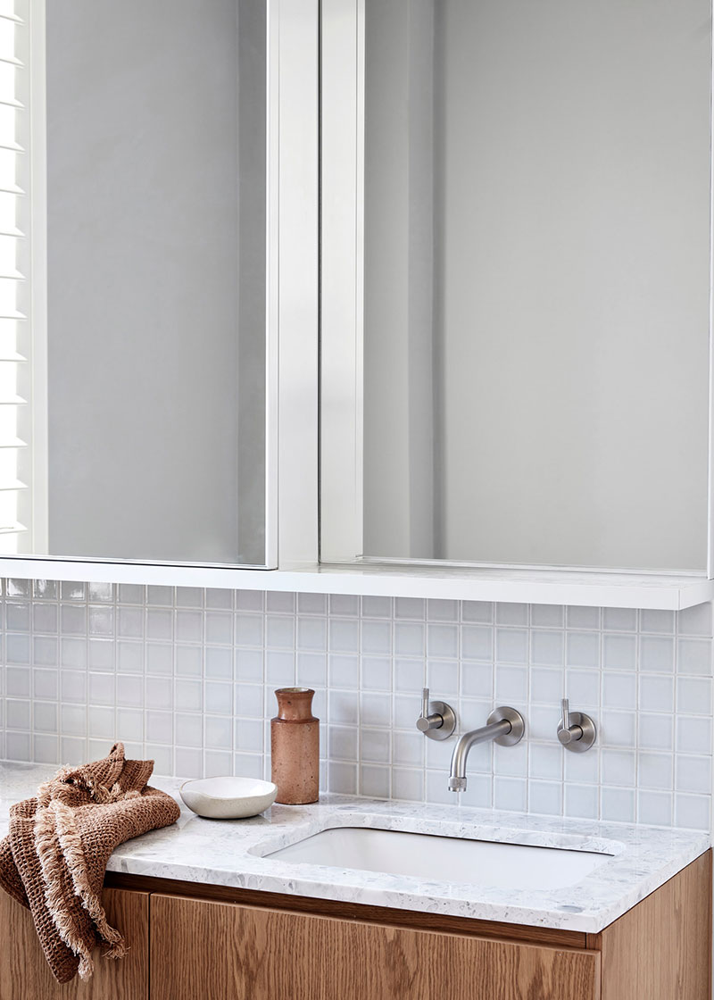 Restrained design of the bathroom with shallow glossy tile, wooden vanity, and white cabinet
