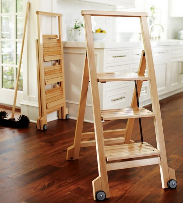 Make Your Cooking Process Easier with Step Up Kitchen Helper. Light wooden stepladder at the backdrop of the dark noble parquet