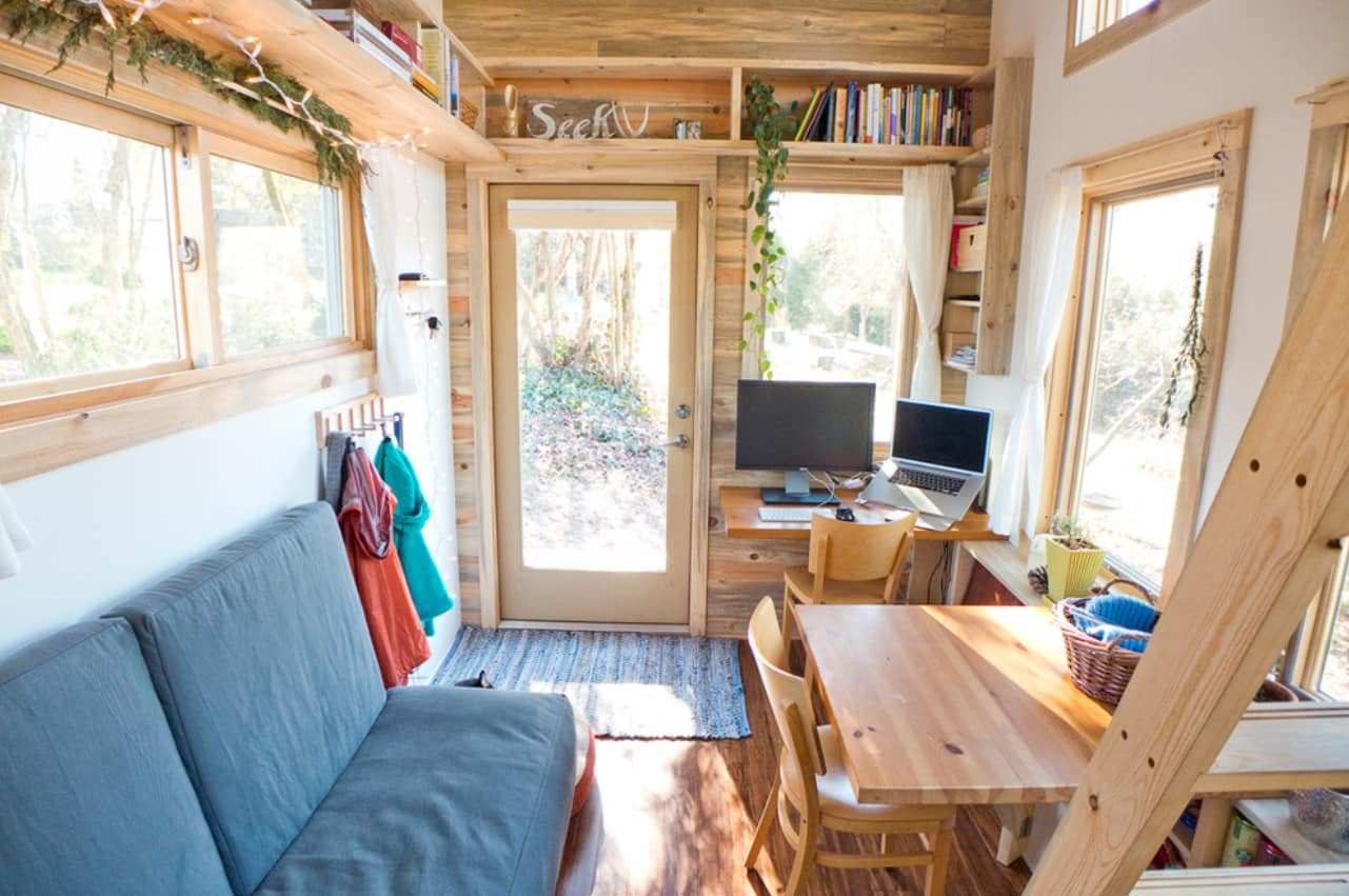 Tiny Home Interiors that Can Inspire Making Your Space more Functional. All-wooden trimming of the well lit wee house with blue couch and dining zone at it