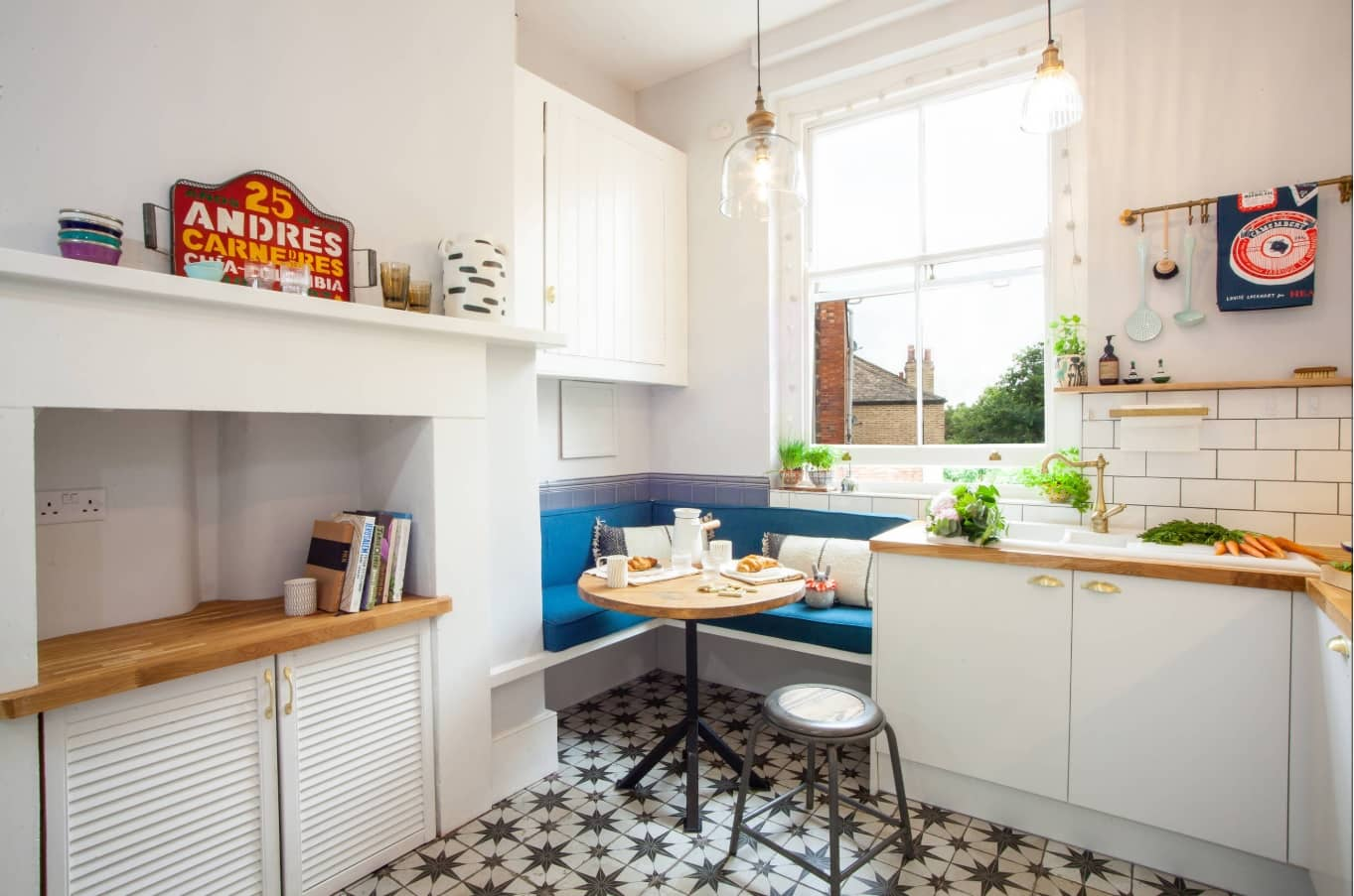 Tiny Home Interiors that Can Inspire Making Your Space more Functional. Dark pattern on the floor of the white decorated kitchen with dining zone at the window