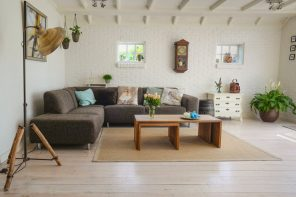 Simple Yet Effective Home Updates to Help You Sell Your Home. Large simple styled minimalistic living zone with dark gray sofa and wooden coffee table