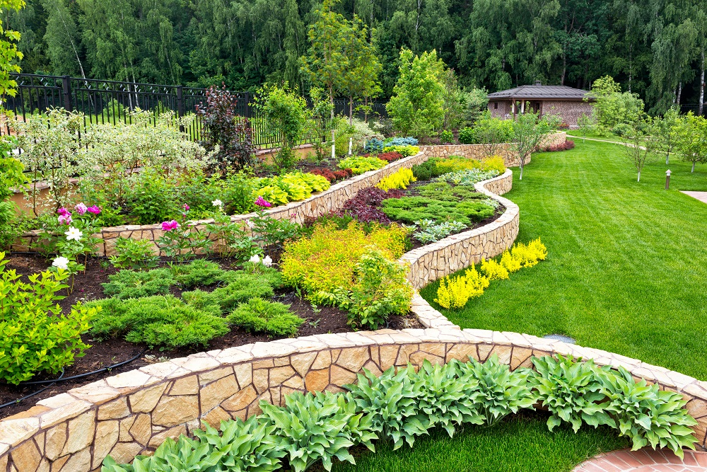 Top 6 Ways Landscaping Impacts Your House. The backyard garden with low stone walls zoning