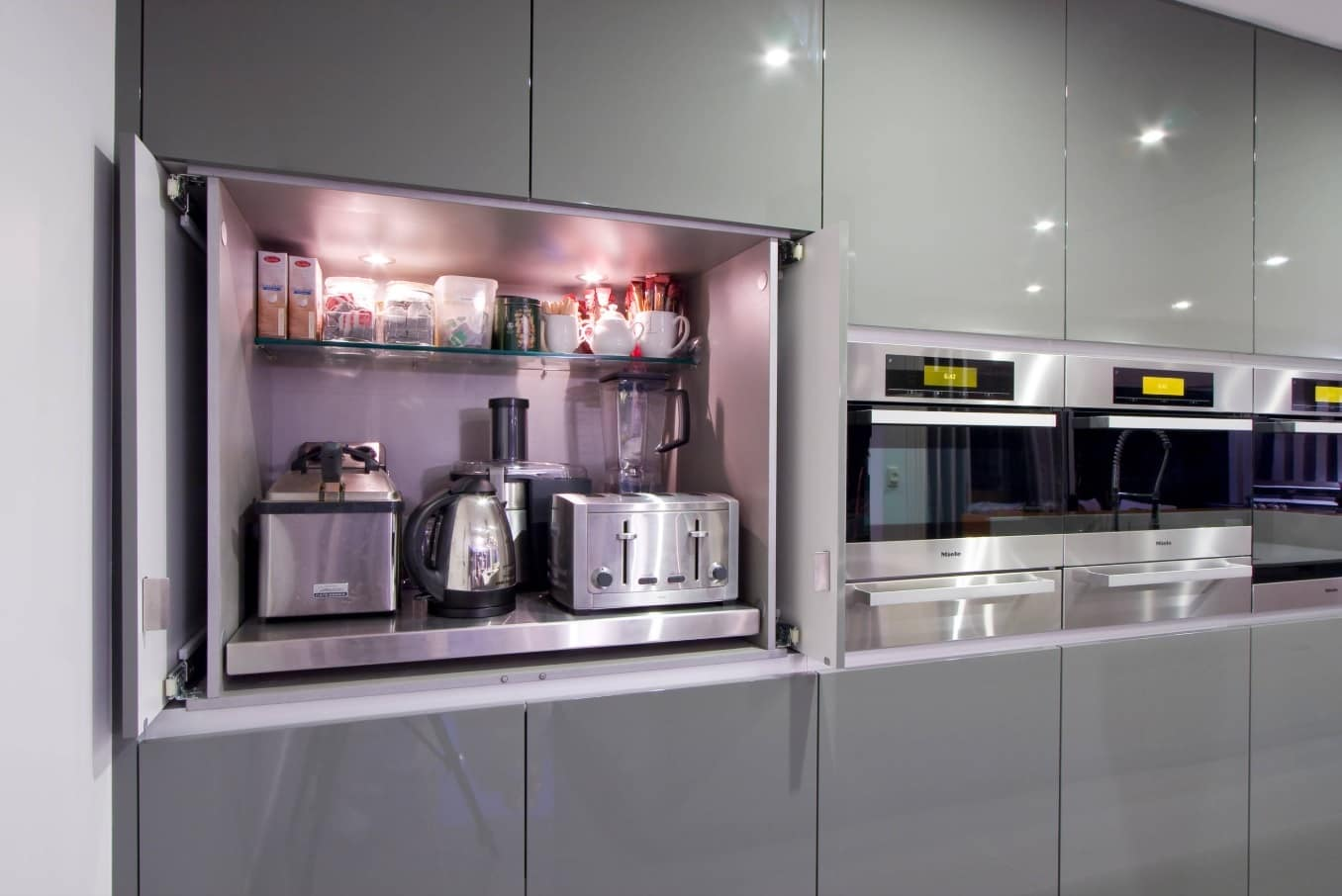 Enhance Home Interior with Stylish Appliances Without Breaking Bank. Modern designed kitchen facades in grey color with the recess for the appliances