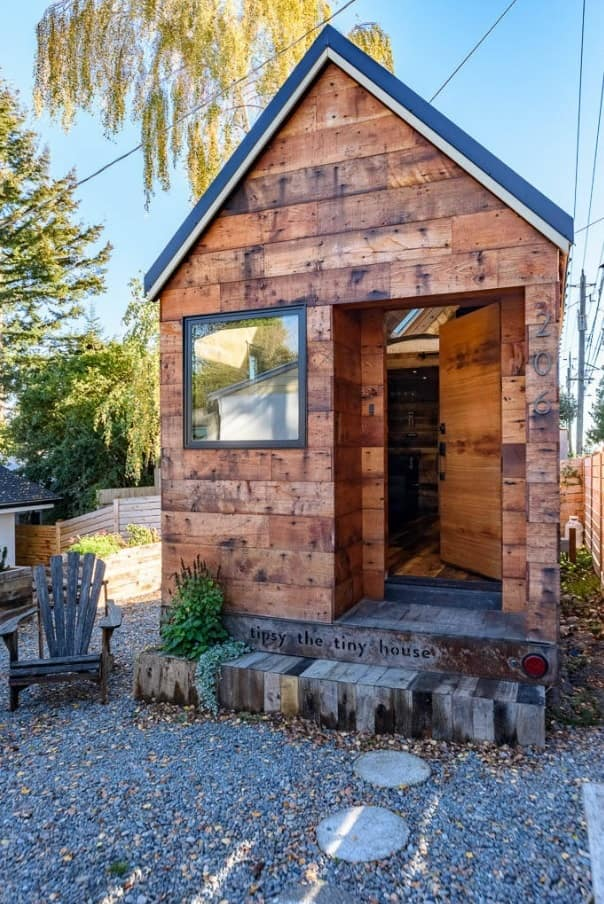 Tiny House on Foundation: Pros and Cons of Living in a Small House. Wooden trimmed house on a small land site with maximum space for living