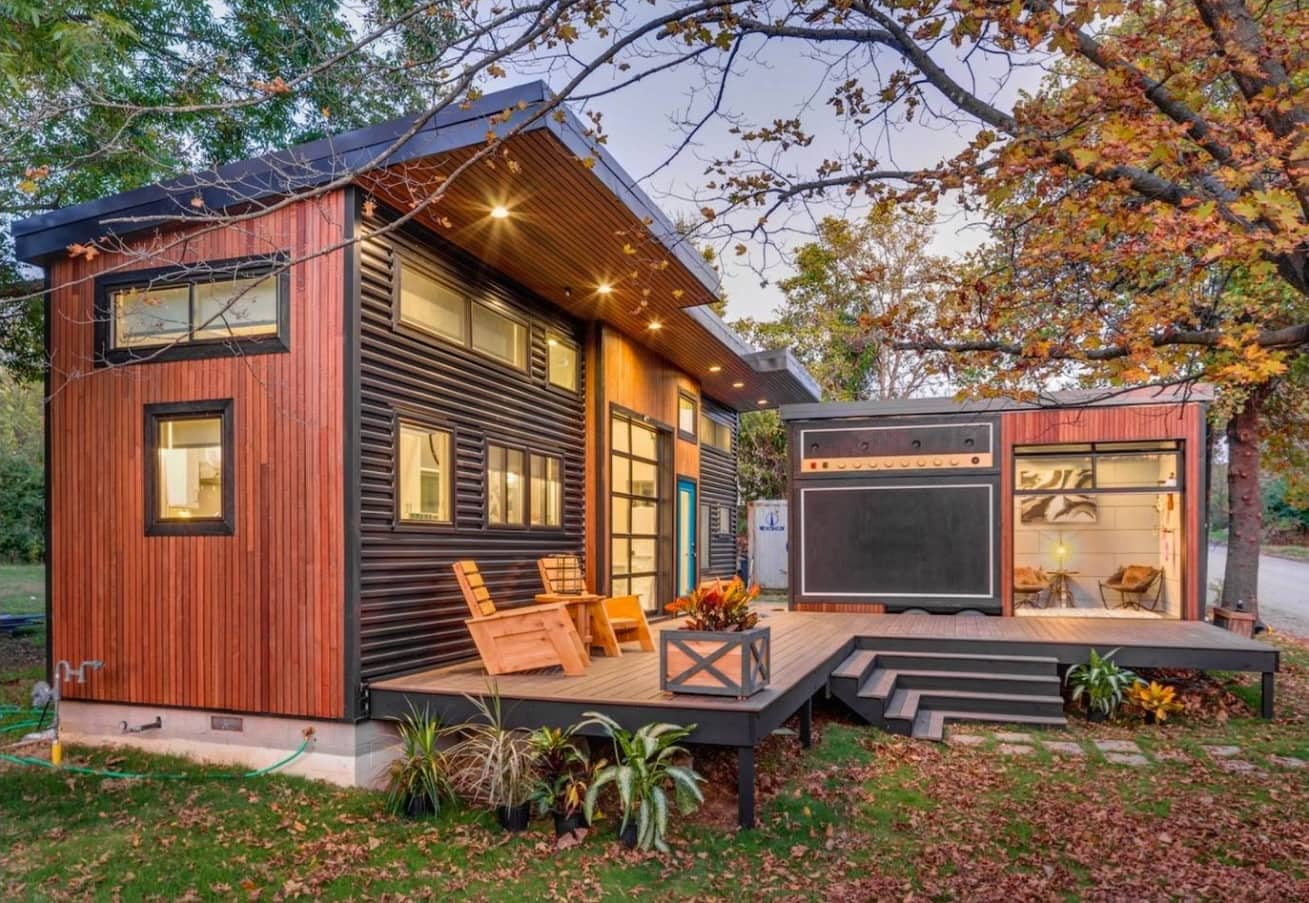 Tiny House on Foundation: Pros and Cons of Living in a Small House. Full-fledged modern house with wooden trimming and a deck with leisure zone