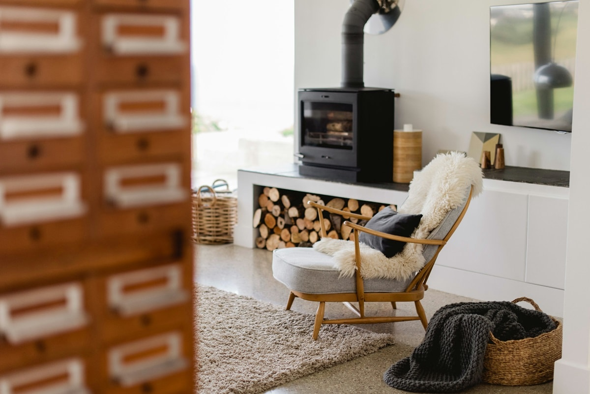 Hygge Interior Design Style and Life Philosophy: Cozy Danish Tradition. Cast iron fireplace and the firewood stack right at the living room