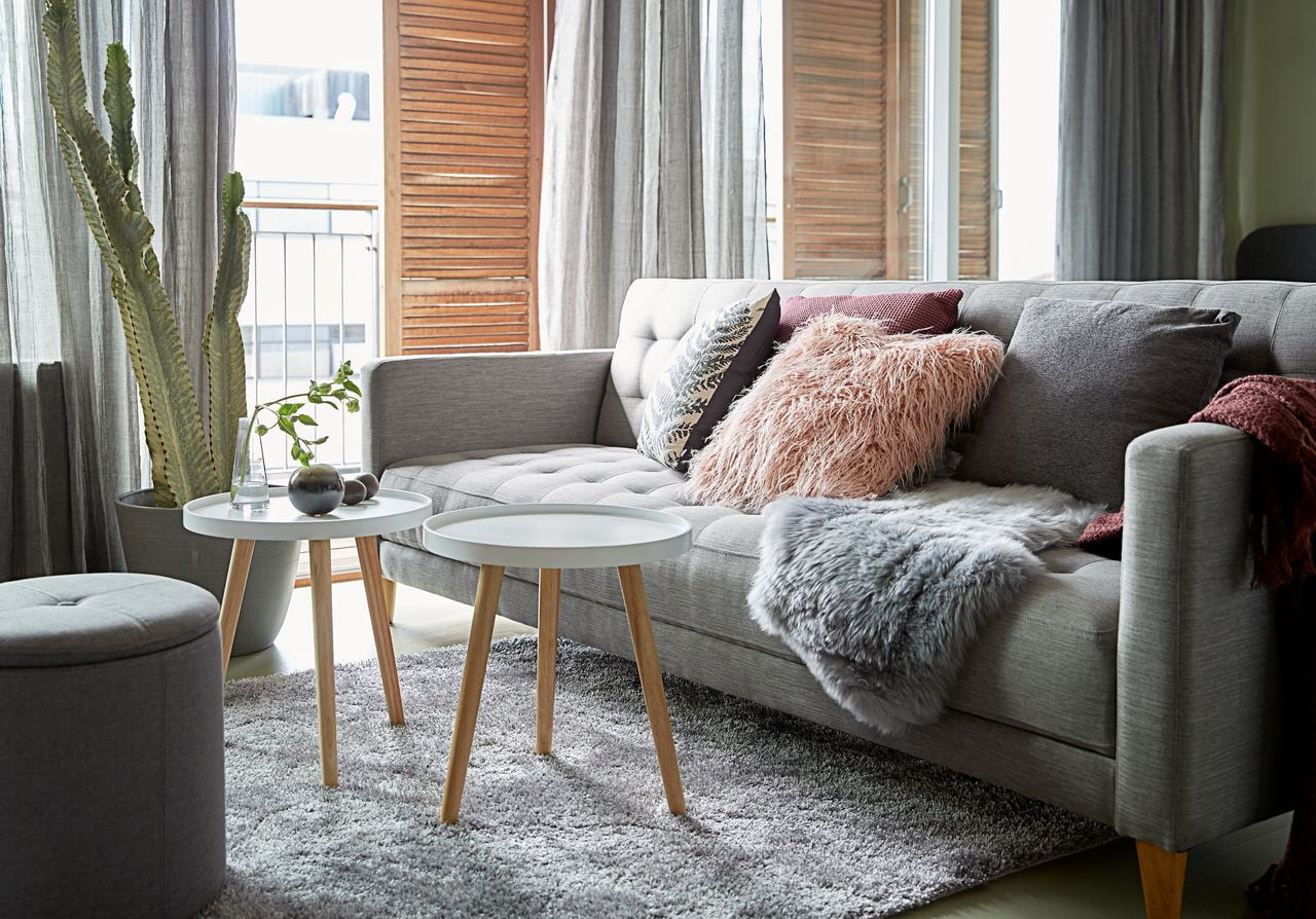 Scandinavian designed apartment with colorful pillows and two gray coffee tables