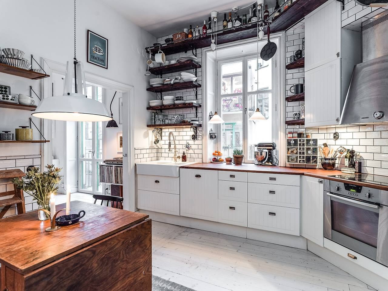 Hygge Interior Design Style and Life Philosophy: Cozy Danish Tradition. White colored kitchen with dark wooden open top shelves