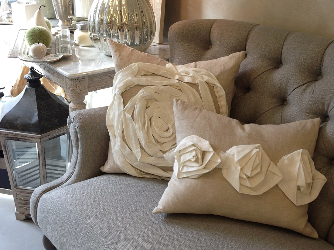 Quilted beige sofa with etxtile white roses embroidered cushions