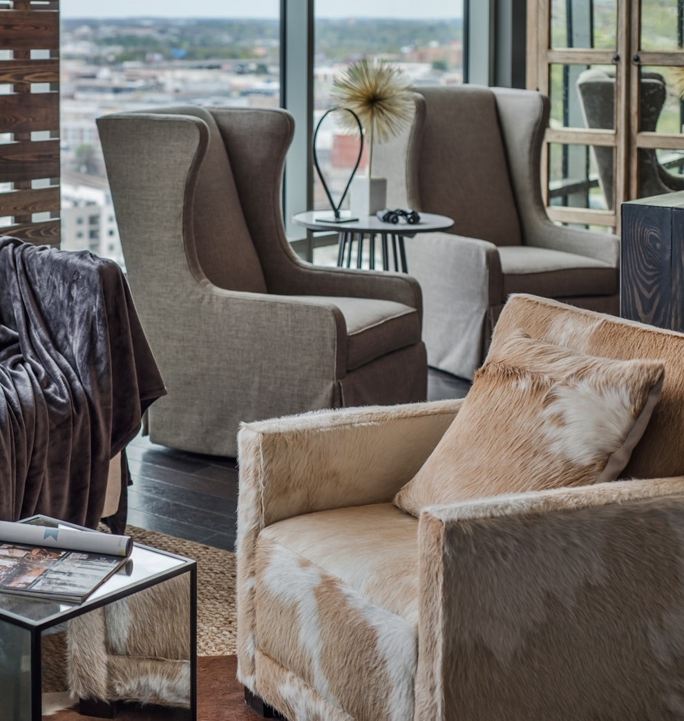 Beige and brown armchairs in the interior of large open layout apartment