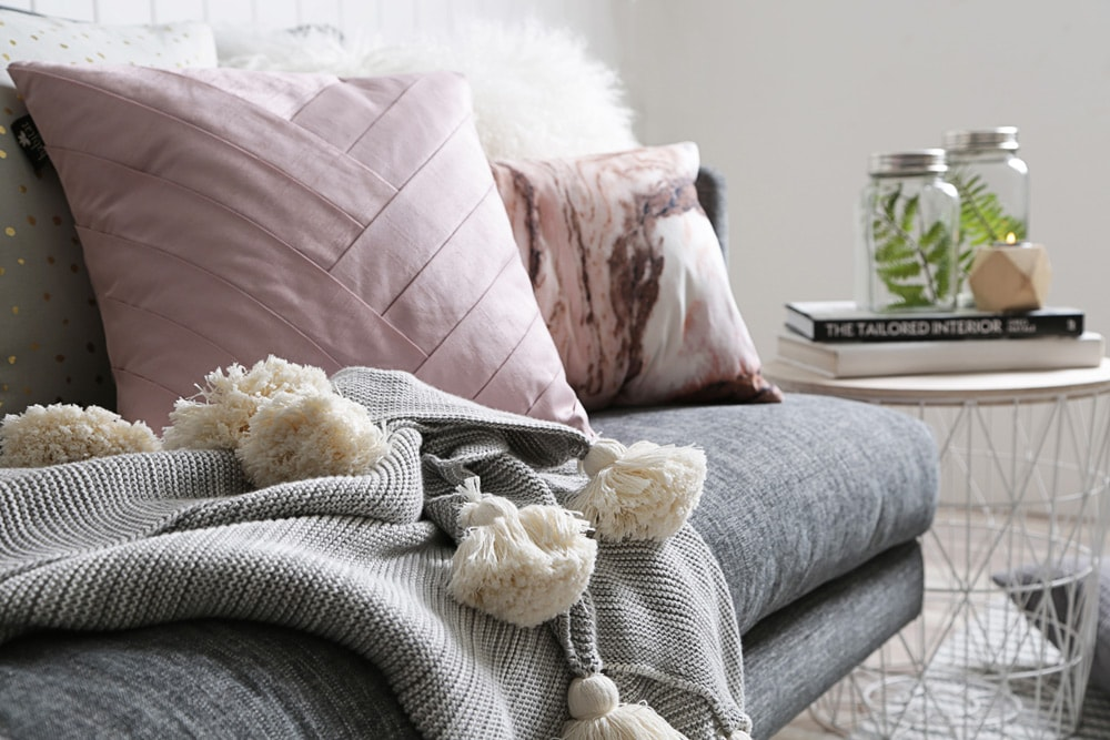 The sofa in the living room with pink pillows and gray blanket