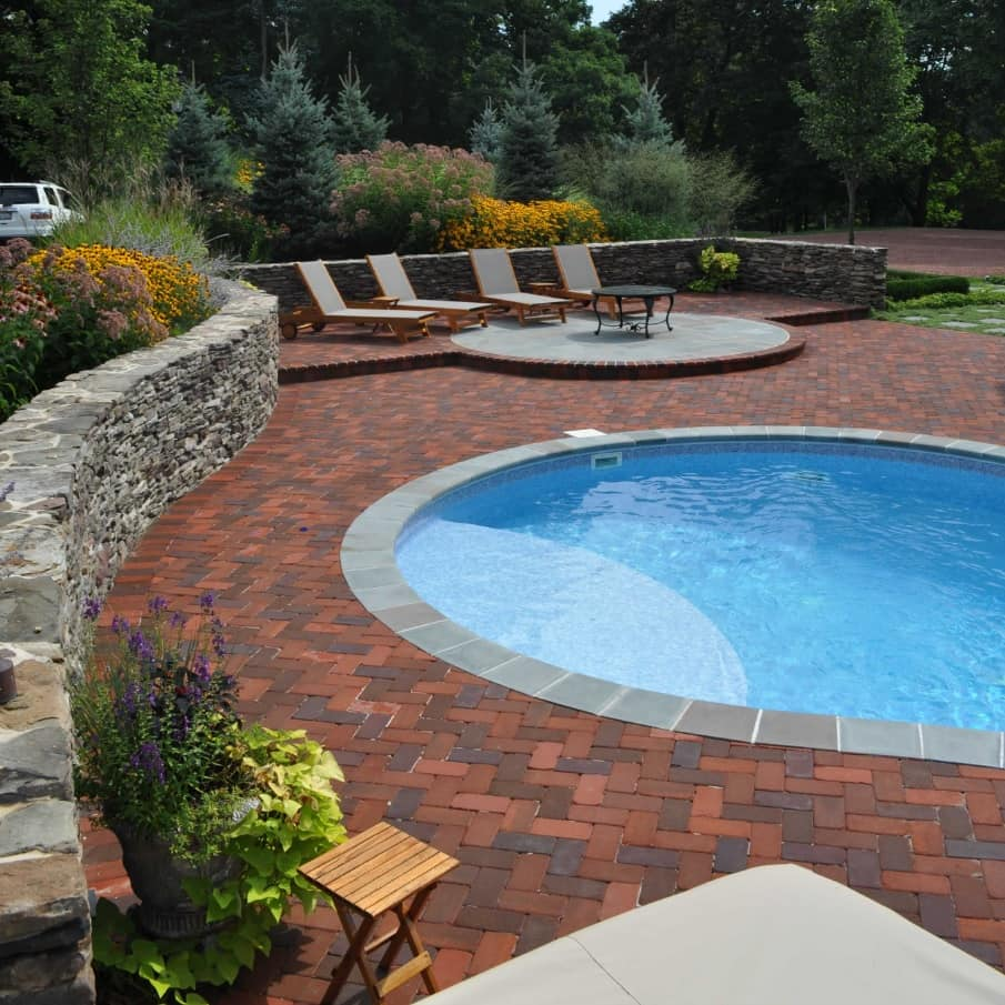 8 Benefits of Installing Brick Pavers. Round pool with leisure area for large mansion with well-groomed garden