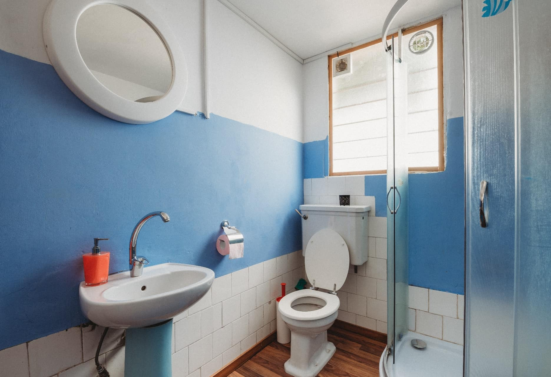 Why Compact Toilets Are Best for Small Bathrooms. Simple casual design of the room with blue colored strip on the wall