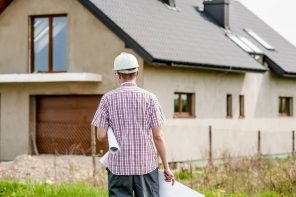 Mistakes to Avoid When Building a New Home. An architect with the plan on the land plot