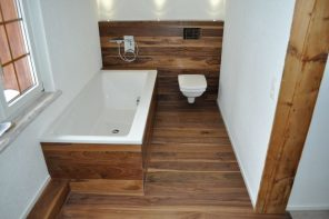 Pros and Cons of Installing Laminate Flooring in Bathroom. Dark wooden laminate including the bathtub and wall facing for modern designed room