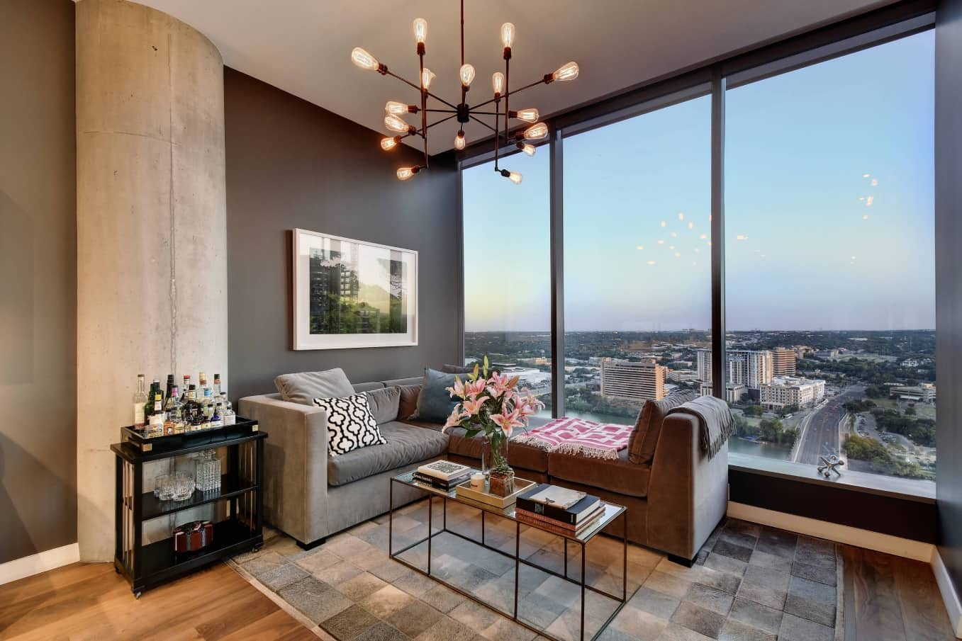 Panoramic windows of the urban apartment with gray accent wall and steampunk elements