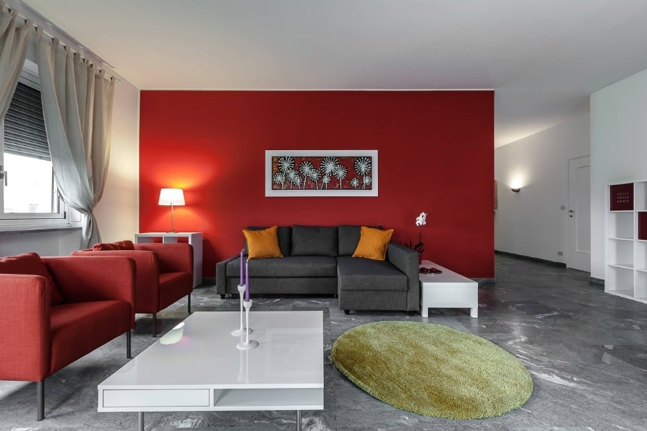 Red Living Room: Elegant & Bright Interior Design. Neat white decorated room with accent red wall with painting over the sofa