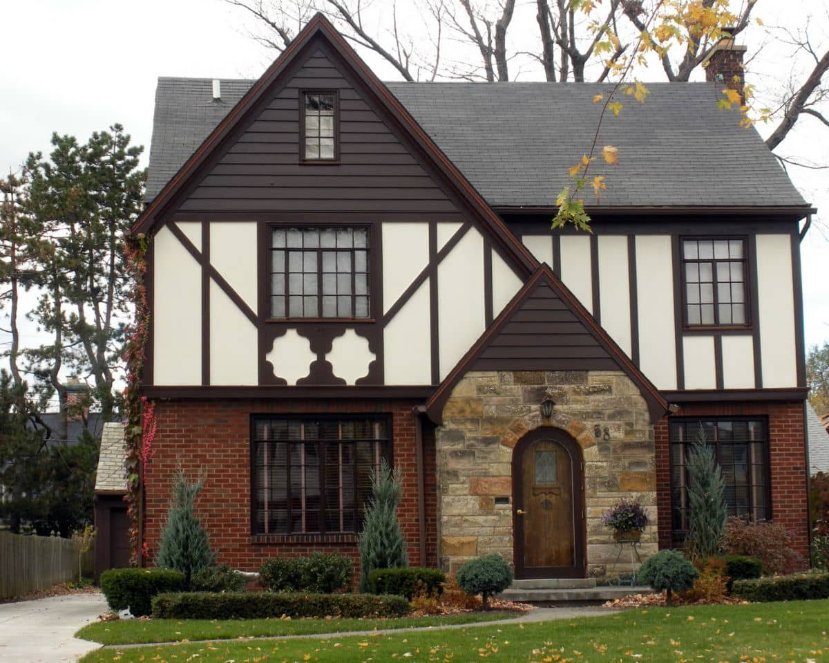 Tudor Interior Design Style History and Examples. White facaded house with stone and dark wooden decoration