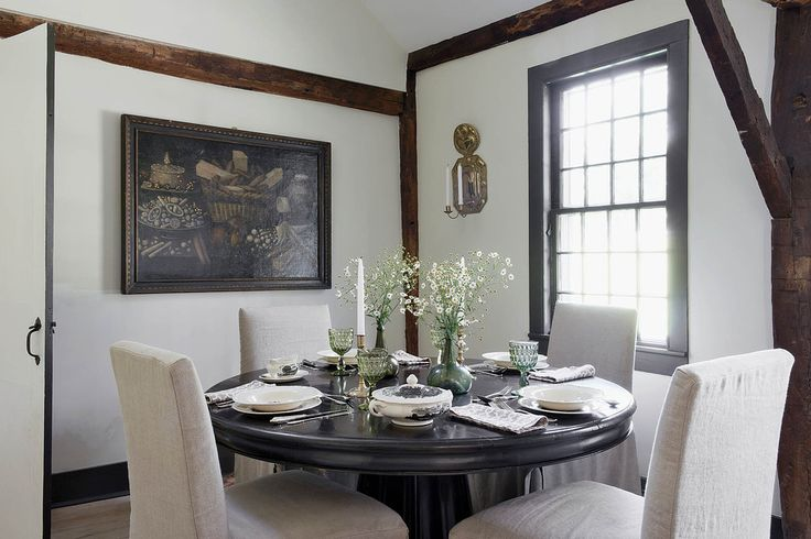 Tudor Interior Design Style History and Examples. White colored walls and wooden beams as a decoration together with black wooden dining table and dark framed sash window
