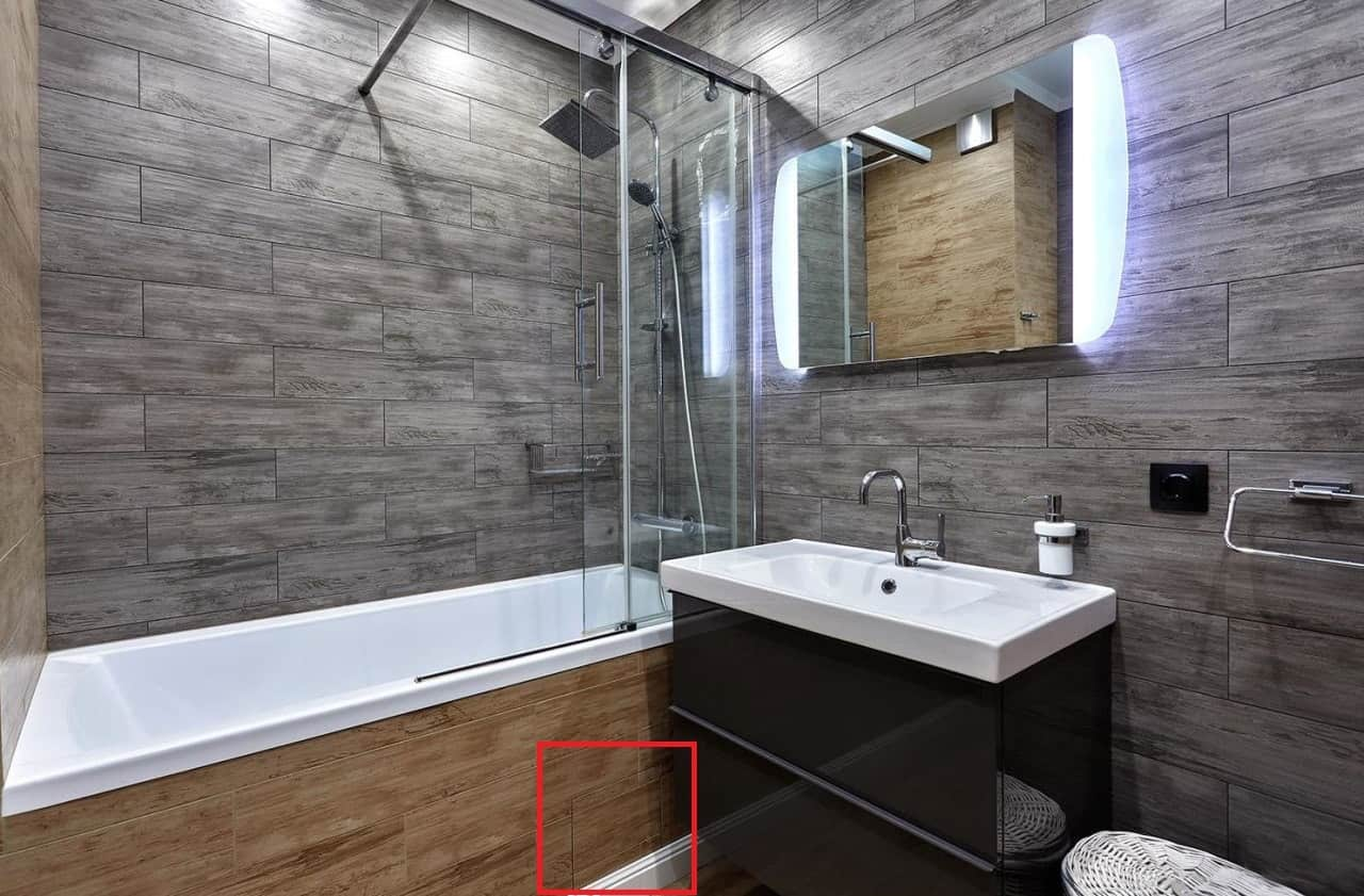 Top 15 Common Mistakes during Bathroom Renovations. Gray tile wall finishing and wooden imitating bathtub side screen