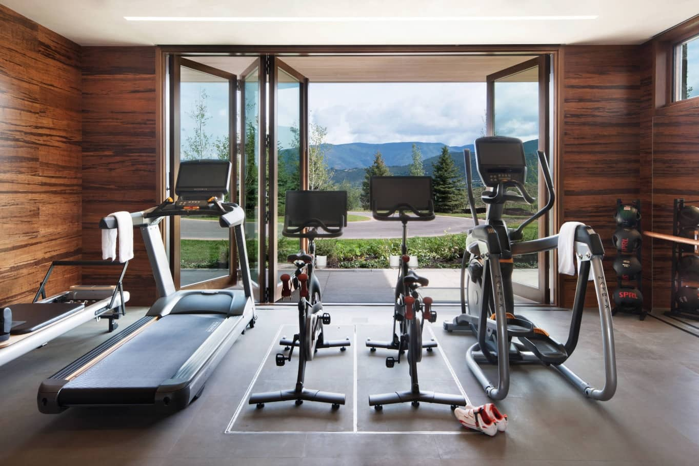 How to Build a Cheap and Effective Home Gym. Chalet styled interior with machine trainers