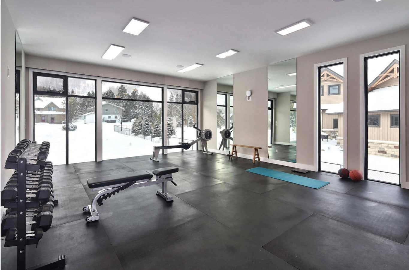 How to Build a Cheap and Effective Home Gym. Large hall of the mountain house with couple of weight benches