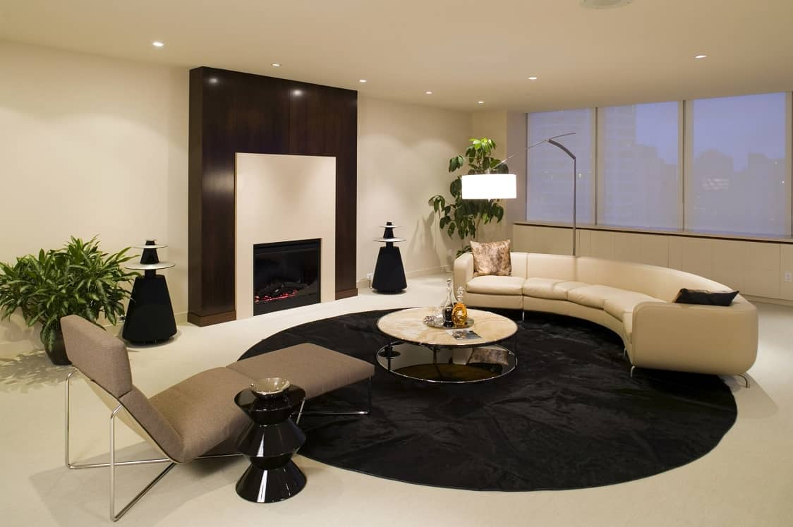 Black round rug to delimeter the living zone in ultramodern beige colored interior