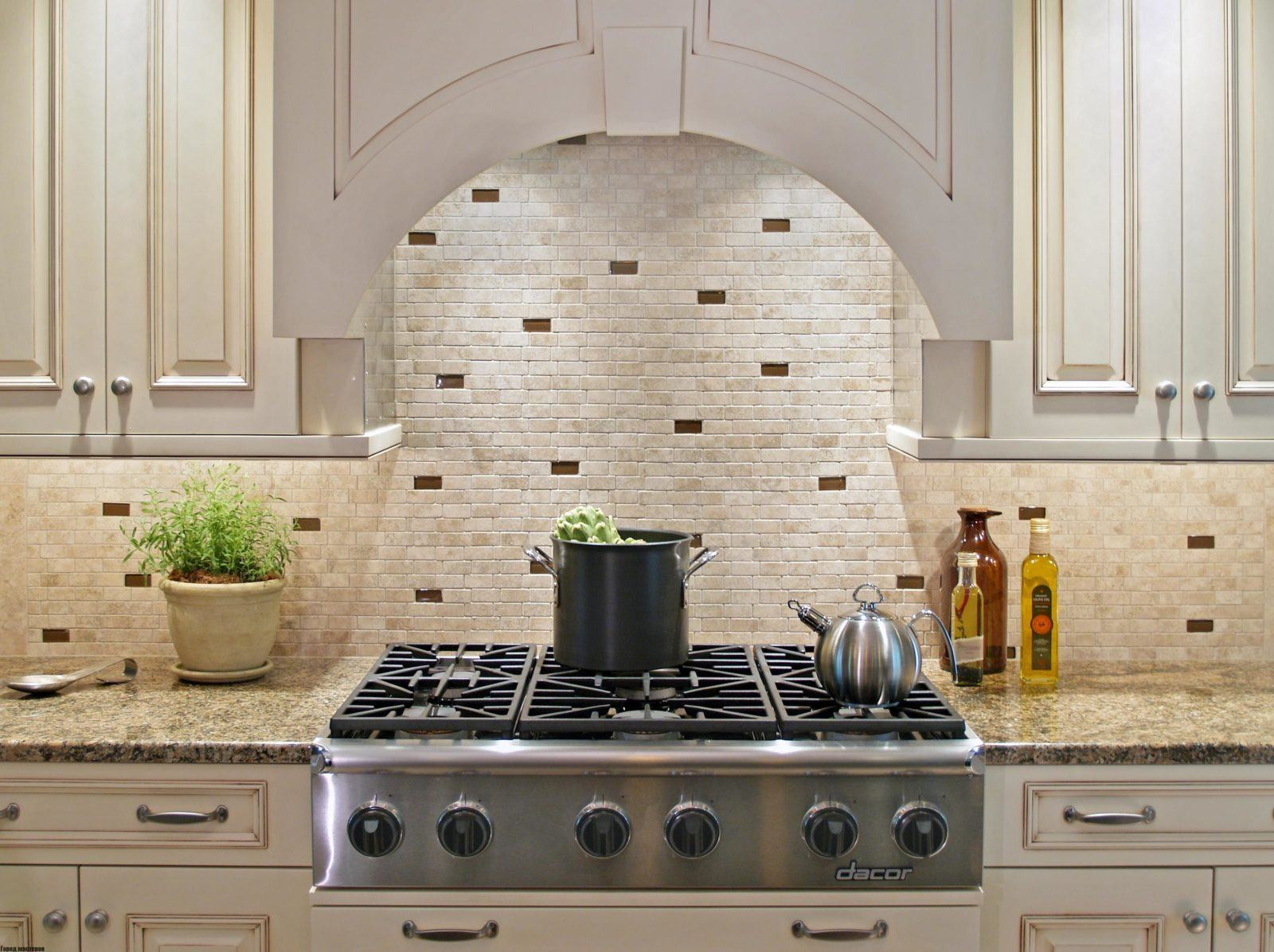Provence designed kitchen with arched hood and mosaic at the hob