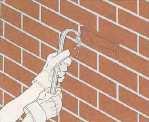 Masonry Pointing: Joints Recovery to Spalling Brick Repair. Removing the spalling brick with the crowbar