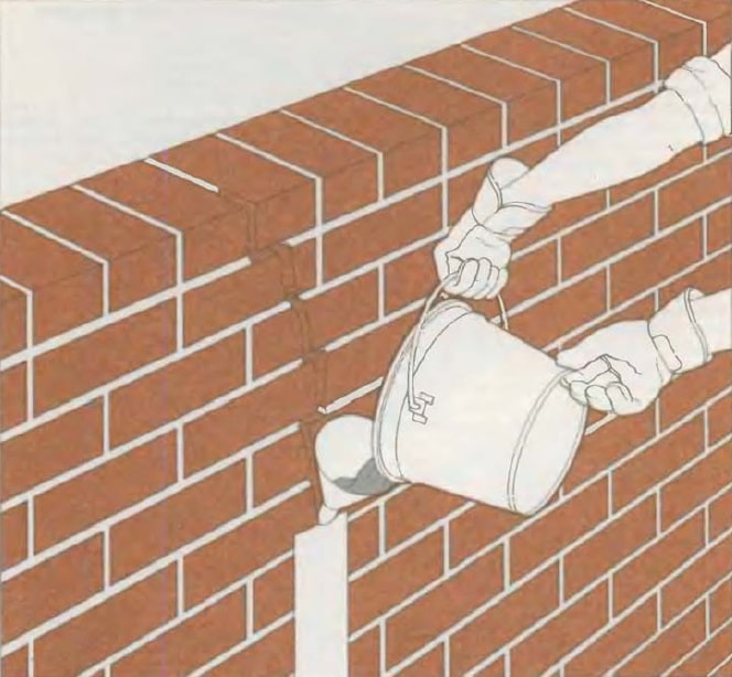 Masonry Pointing: Joints Recovery to Spalling Brick Repair. pouring the wall crack with mortar
