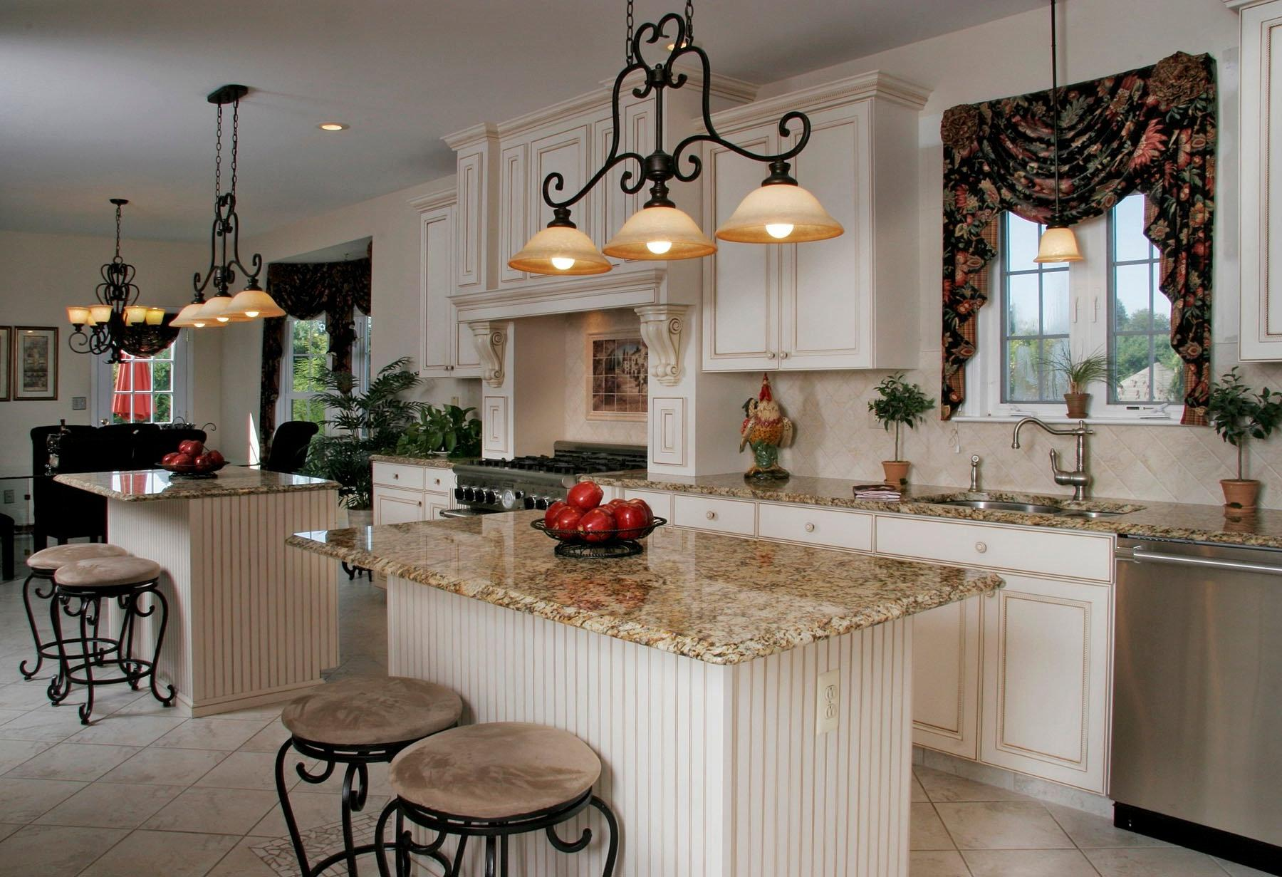 Wrought iron chandelier over the glossy beige marble top of the island
