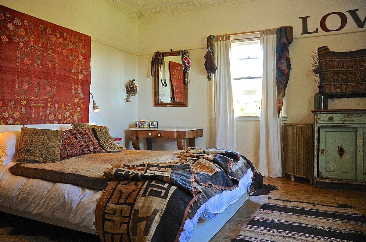 Ethno stylistic in the small bedroom with red carpet on the wall