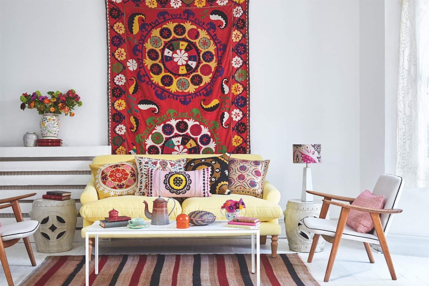 Colorful living room interior with carpet on the wall and other motley decoration